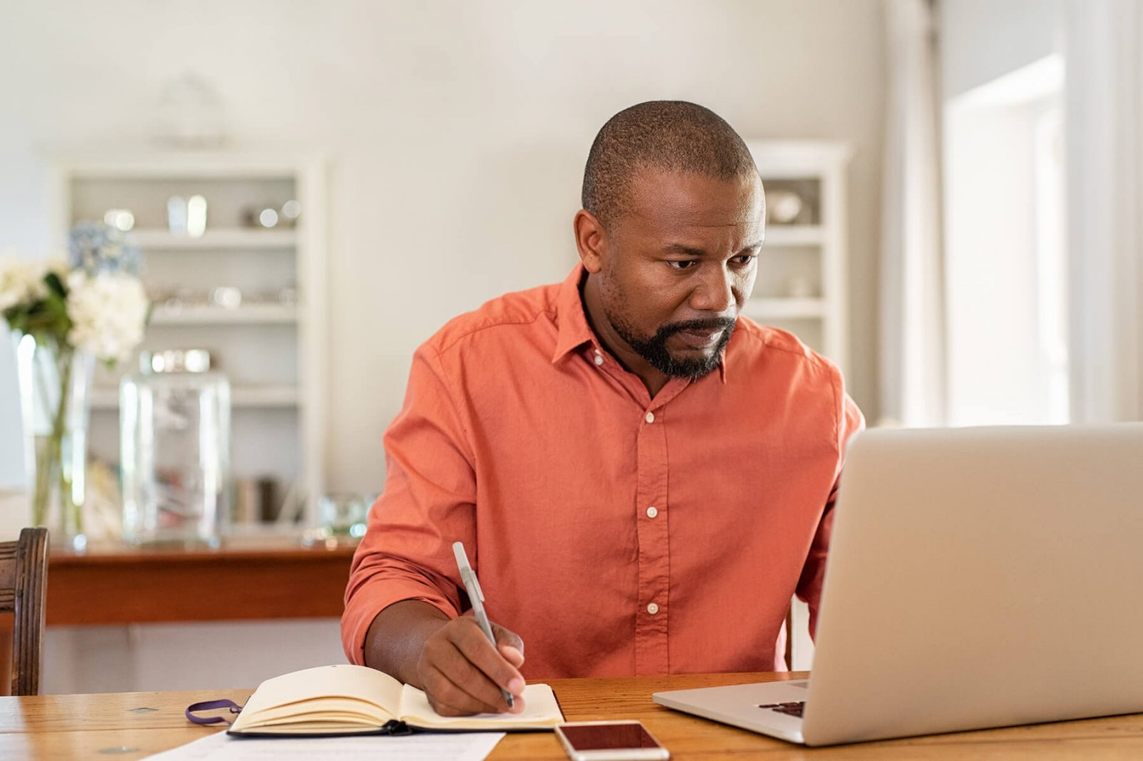 man studying from laptop at home
