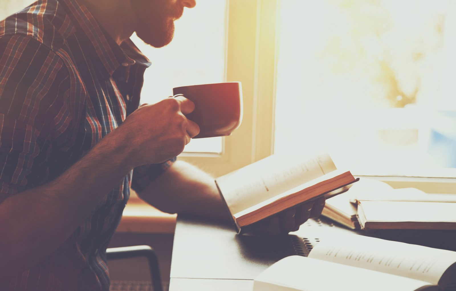 someone drinking coffee while reading the bible