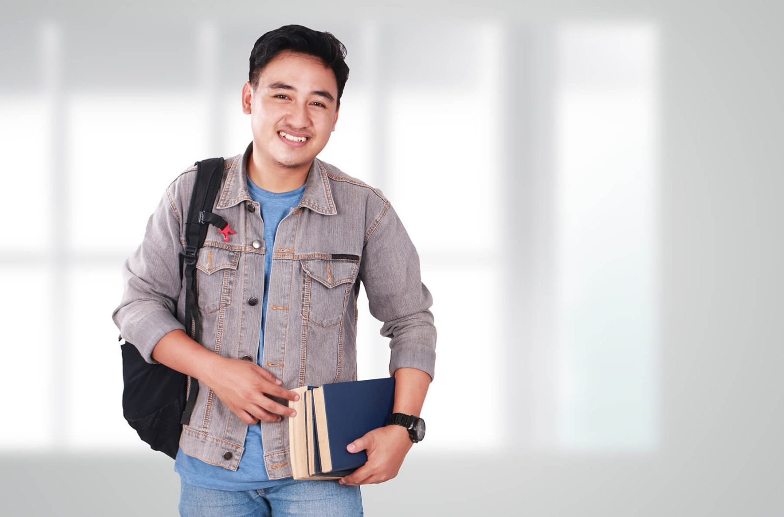 smiling male holding books