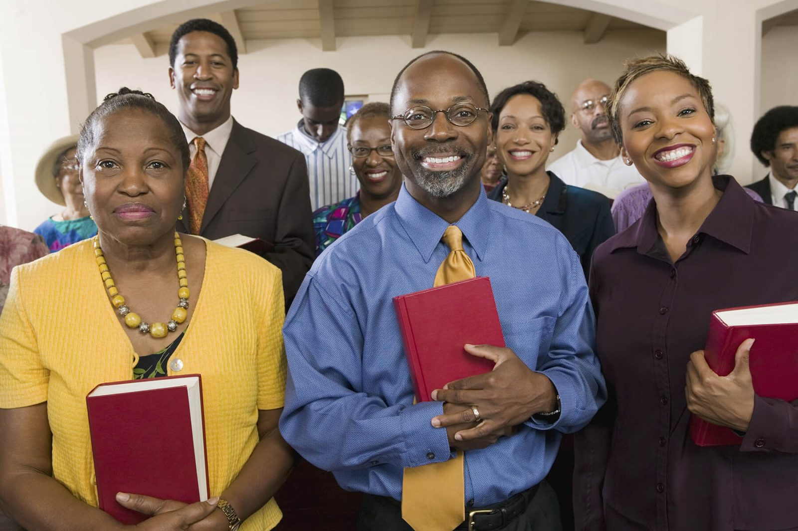 smiling African American people standing with bibles in the church