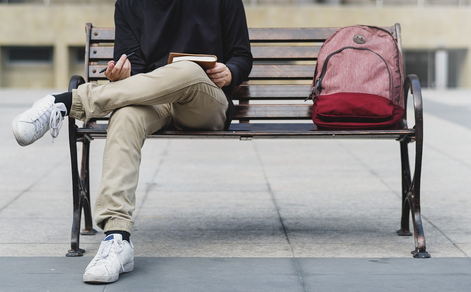 student man writing diary chilling on bench