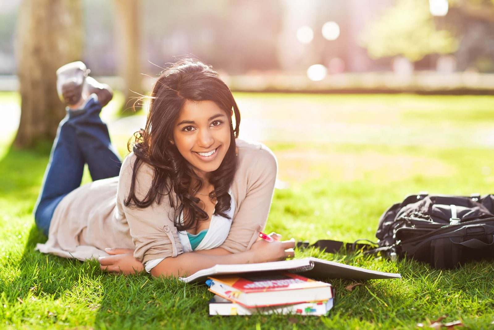 student studying on campus lawn