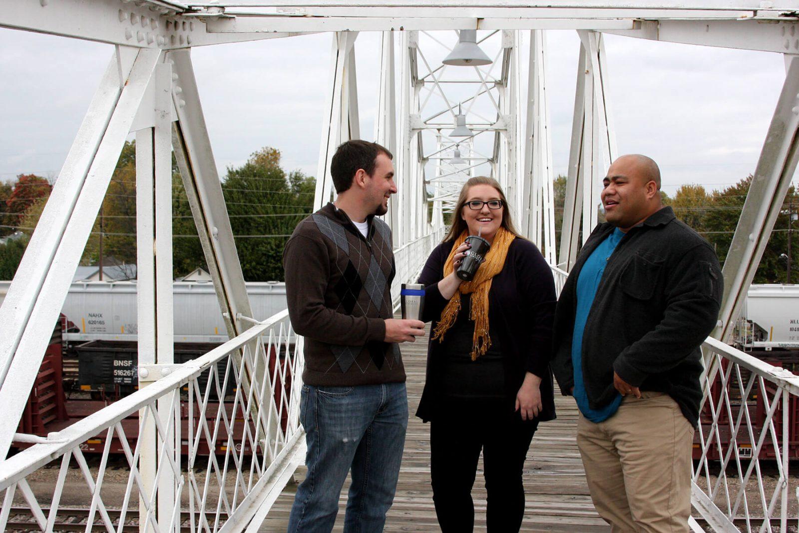 Three Global Students on walking bridge talking