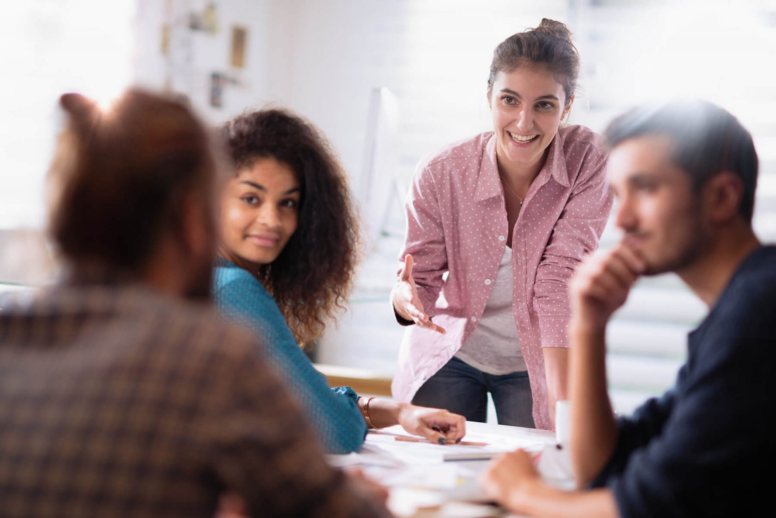 young woman leads office meeting