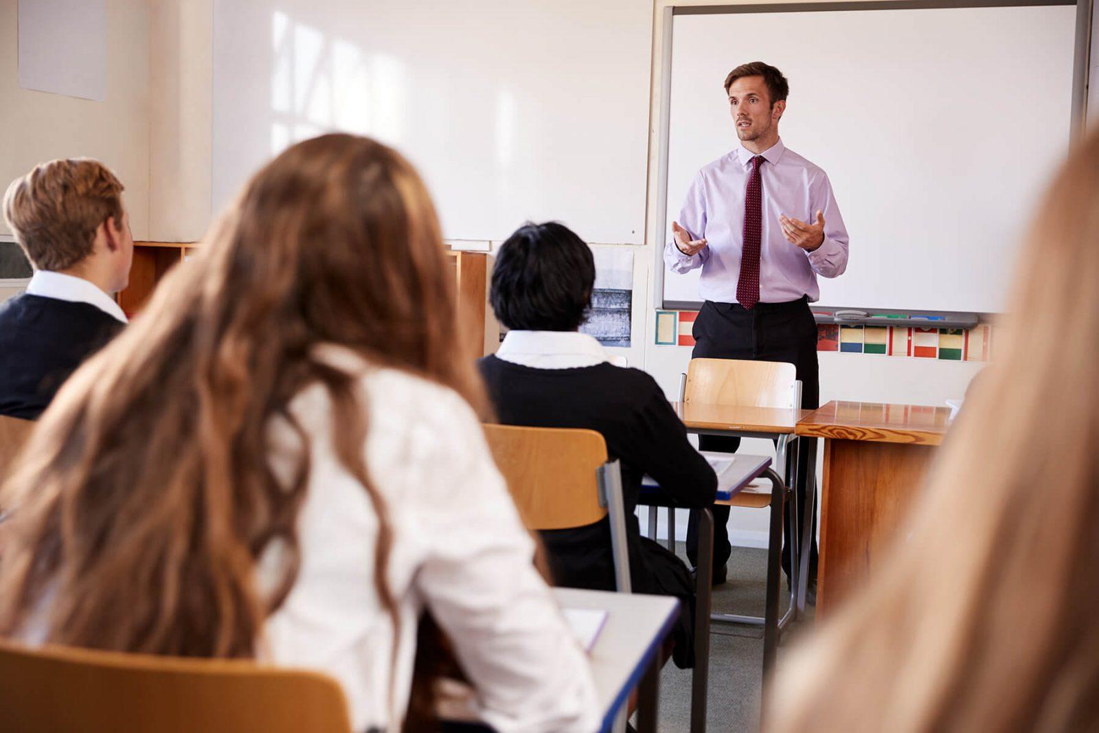 teenage students listening to male teacher