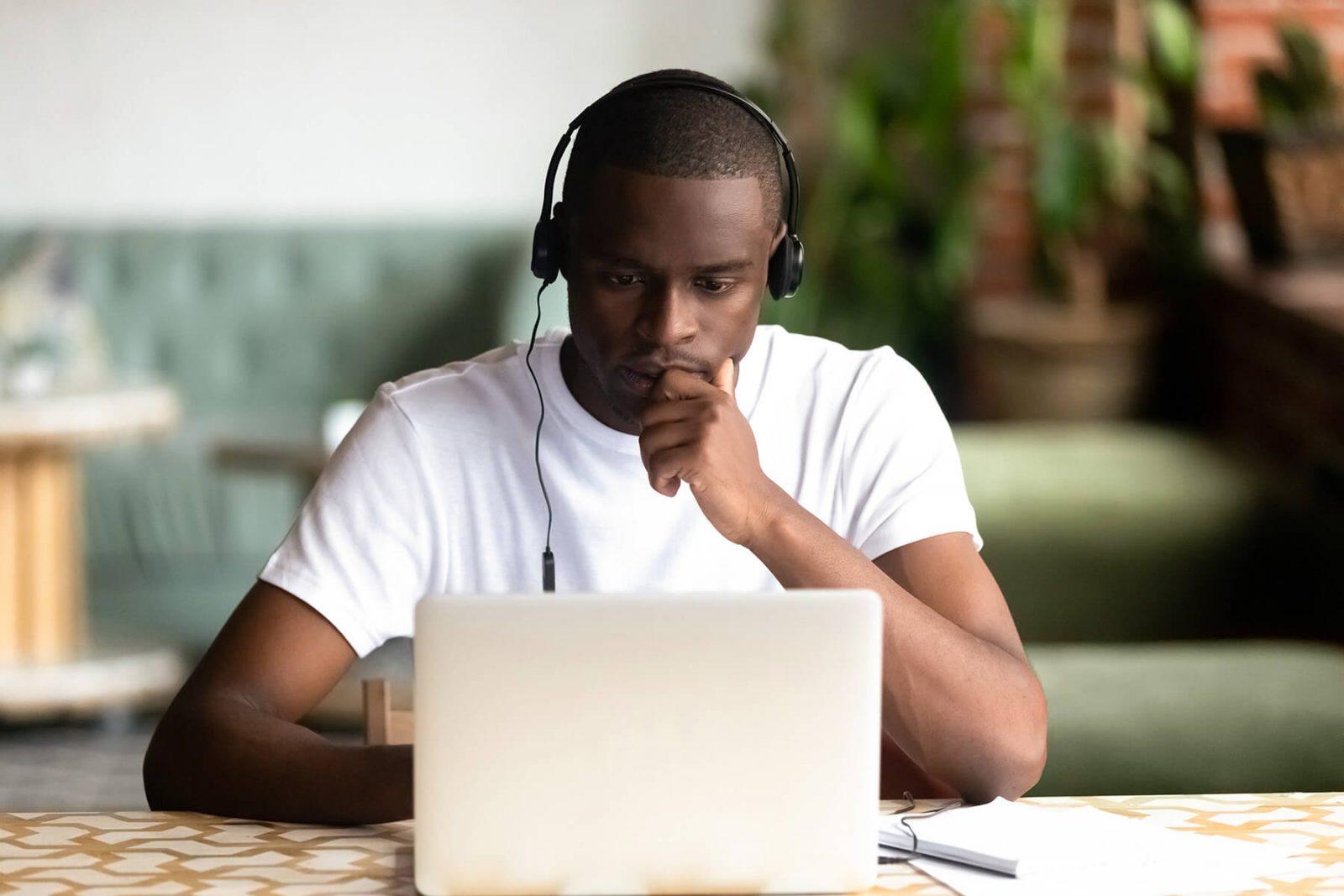Focused African American man wear headphones using laptop