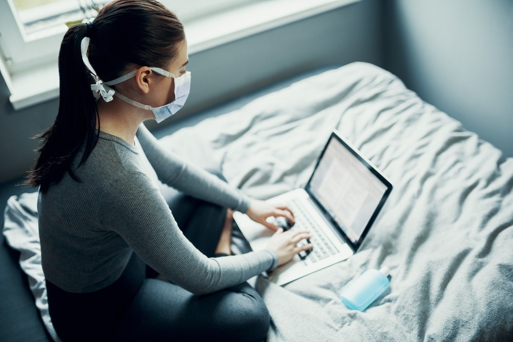 Young woman learning at home with mask on in front of computer for COVID-19