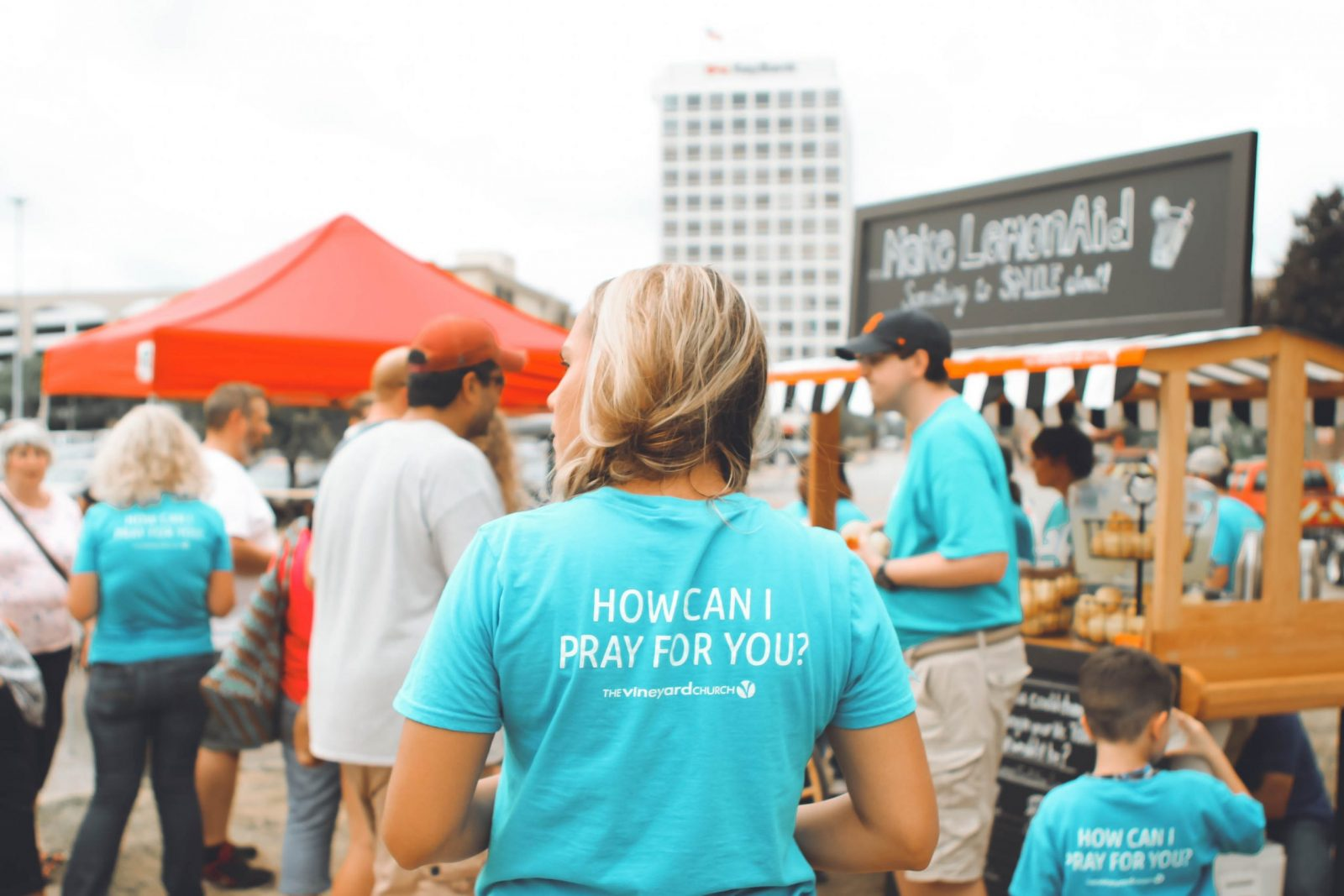 Church volunteer at an outdoor food market among a crowd of people