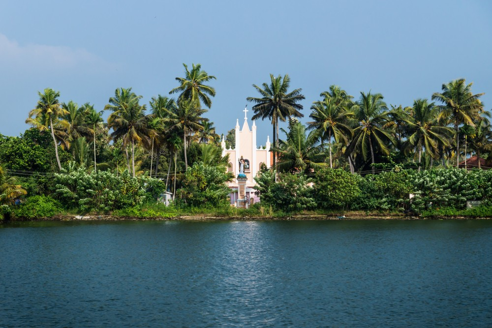 Beautiful white church building among palm trees in Kerala, India