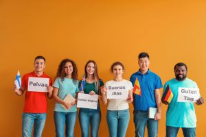 Young multi-ethnic students hold pages displaying different languages