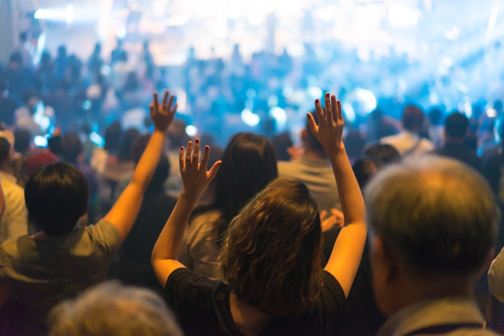 Hands raised during a church service with a large gathering