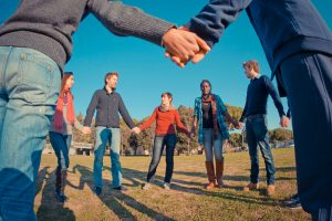 Multi-ethnic group of young people holding hands