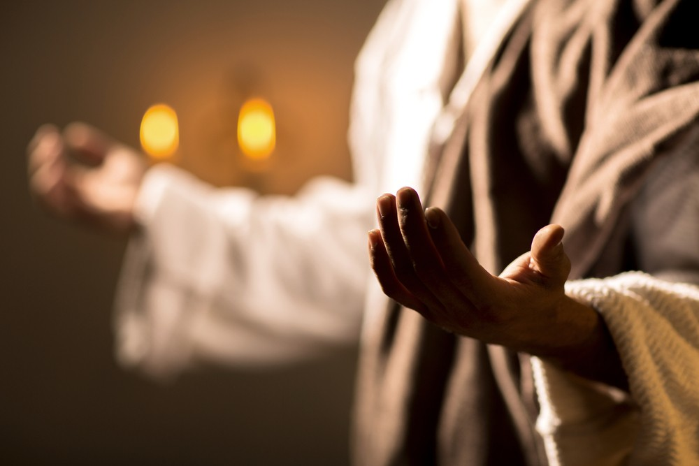 Person dressed in robes praying with palms facing upward