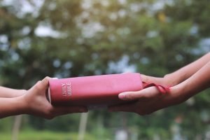 Two sets of hands touching a Bible representing evangelism