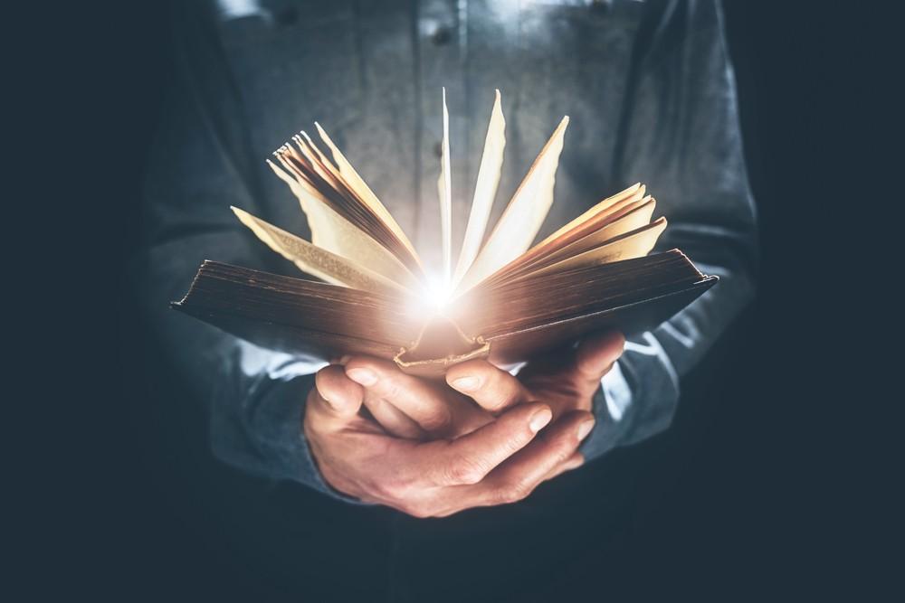 Man holding glowing Bible