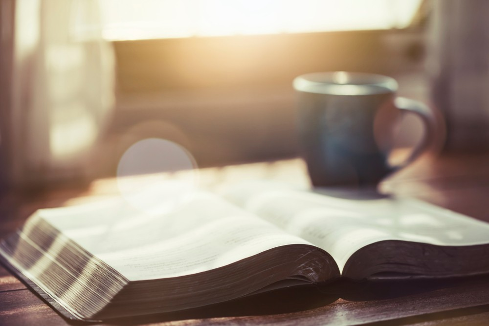 Open bible on coffee table with mug in the background