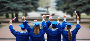 Backs of graduates in caps and gowns holding diplomas in the air celebrating