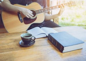Man player a guitar in front of a bible and hymnal on coffee table