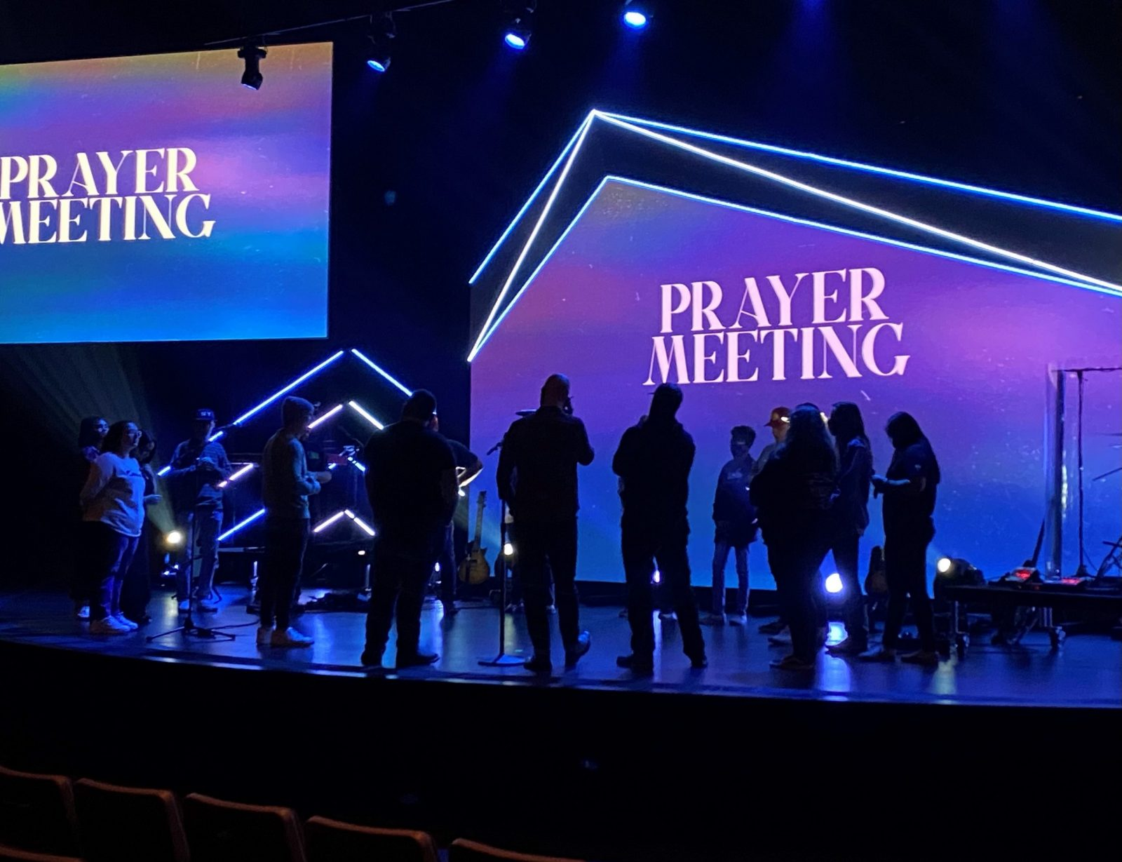 People on stage praying before church service