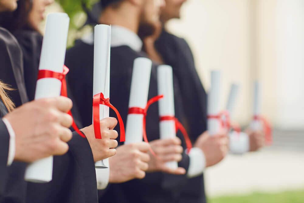Line of graduates holding diplomas