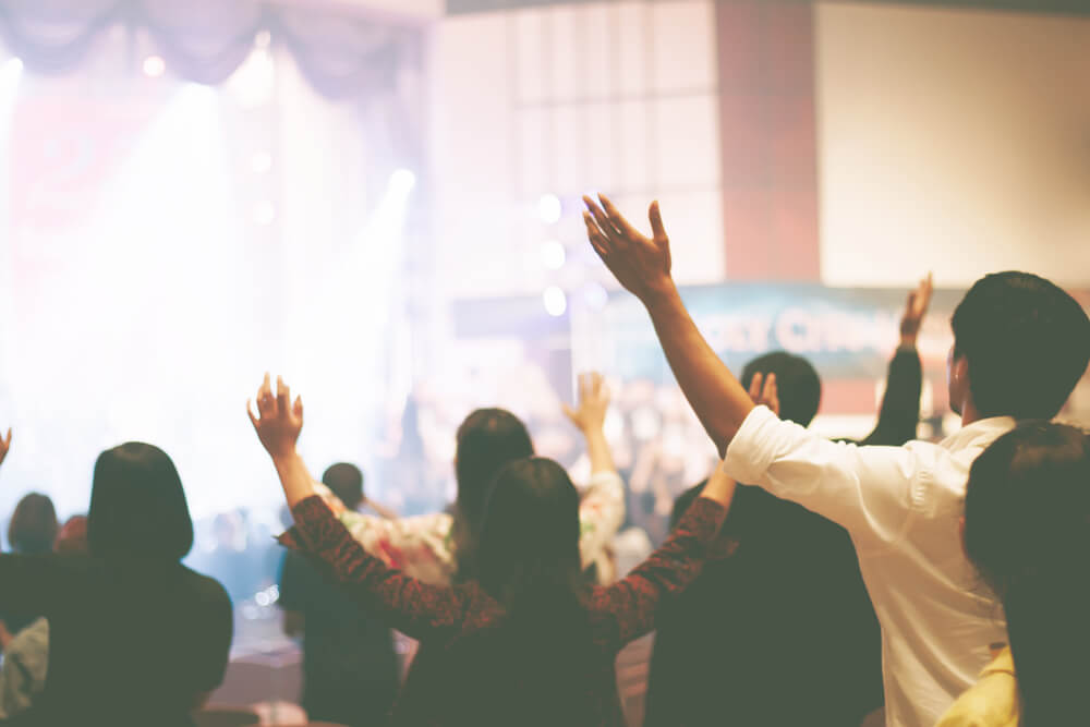 Group of people worshiping in front of a stage with hands up
