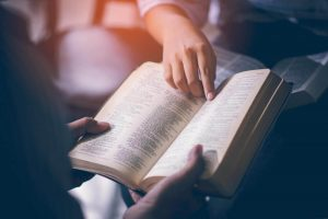 Two people holding and reading a bible together