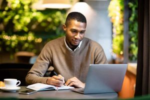 Young distance learning student working on a laptop